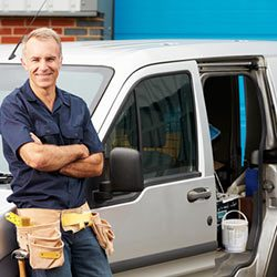 tradie-with-arms-folded-leaning-on-his-van